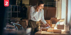 A imagem mostra uma mulher falando no telefone e gerenciando os pedidos do seu empreendimento. Simbolizando que criar loja virtual pode não ser um trabalho fácil, mas é traz muitos resultados para sua operação