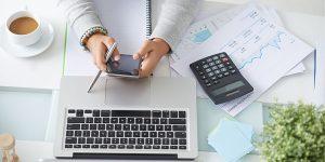 Mulher analisando dados no celular, computador e calculadora. Representando a necessidade da gestão financeira para uma empresa.