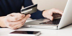 Homem fazendo compra na internet. Simbolizando a importância de integrar loja física e virtual.