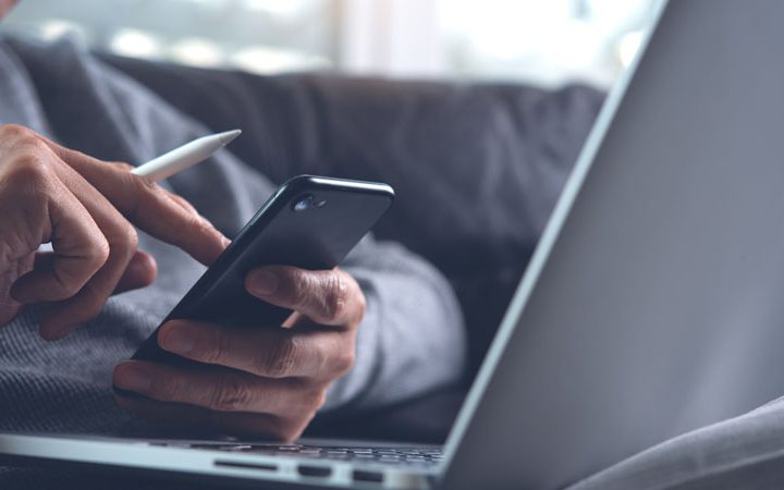 Empreendedor mexendo no smartphone e computador. Se questionando porque sua loja virtual não vende.