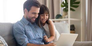 Pai e filha felizes com notebook no colo. Simbolizando compras online realizadas em uma loja virtual que aplicou estratégias para vender mais no Dia dos Pais.