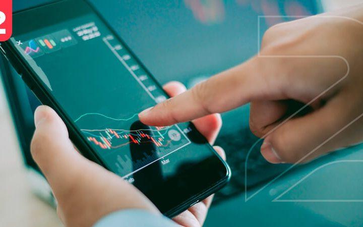 Homem mexendo no smartphone exibindo gráfico de vendas caindo. Simbolizando que cadastrar produtos no marketplace de forma errada pode ser o que motiva suas vendas a caírem.