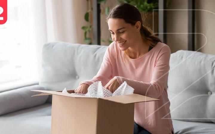 Mulher abrindo uma encomenda feliz com seu pedido, mostrando a importância de saber como fidelizar clientes no e-commerce