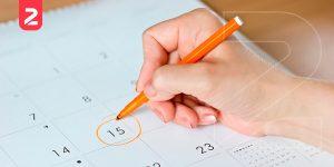 Mão de uma mulher segurando uma caneta em que risca circula um dia no calendário. Isso simboliza a importância de programar as datas comemorativas no e-commerce.