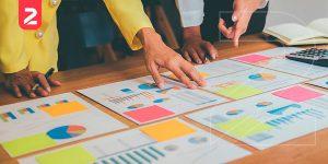 Imagem de pessoas analisando gráficos sobre uma mesa e fazendo o planejamento de vendas online.