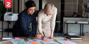 Duas mulheres escrevendo em papéis que simbolizam o planejamento estratégico, tático e operacional no e-commerce