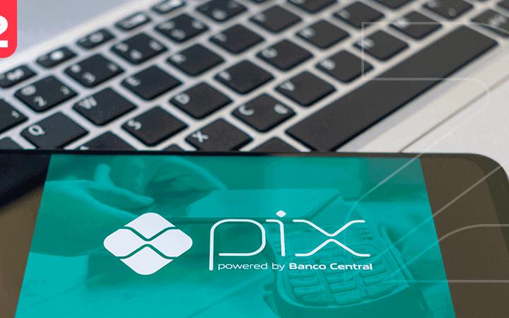 Imagem mostra celular com o que é o Pix, com o notebook ao fundo.