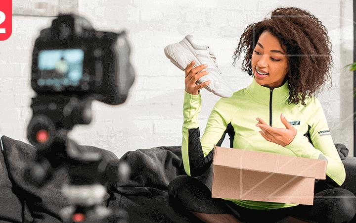 Influenciadora digital mostrando um tênis na frente de câmeras. Simbolizando o quão importante é estabelecer parcerias para loja virtual vender mais.